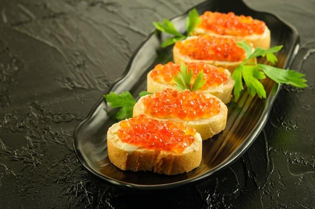 Caviale rosso fresco applicato sulle fette di pagnotta bianca sul piatto nero e sullo sfondo nero.