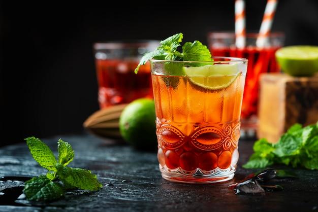 Cocktail fresco rosso con ghiaccio e calce