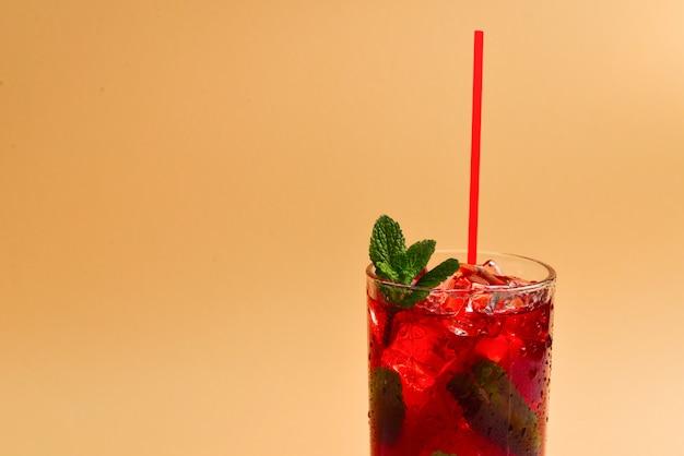 Bevanda fresca rossa con ghiaccio, pompelmo e menta su fondo beige. spazio per testo o design.