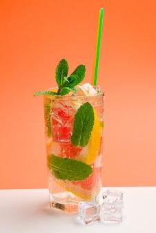 Bevanda fresca rossa con ghiaccio, pompelmo e menta sull'arancia
