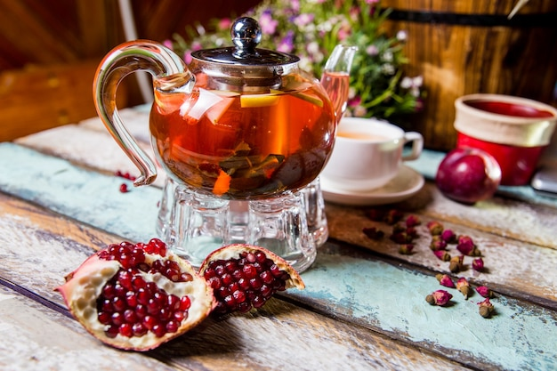 Tè ai frutti rossi in teiera con melograno sul tavolo