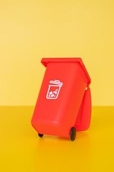 Contenitore di rifiuti rosso su sfondo giallo