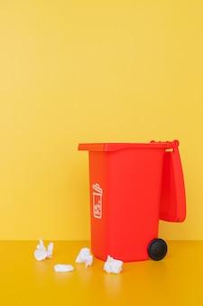 Contenitore di immondizia rosso sulla parete gialla