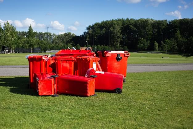 Contenitori di immondizia rossi sull'erba verde nel parco sulla superficie del cielo blu.