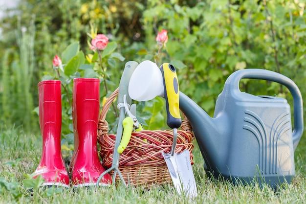Stivali di gomma da giardino rossi, piccolo rastrello, potatore, cesto di vimini, cazzuola e annaffiatoio di plastica su erba verde con sfondo verde sfocato. strumenti per il giardinaggio