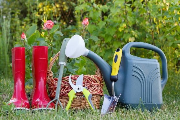 Stivali di gomma da giardino rossi, piccolo rastrello, potatore, cesto di vimini, cazzuola e annaffiatoio di plastica su erba verde con sfondo verde sfocato