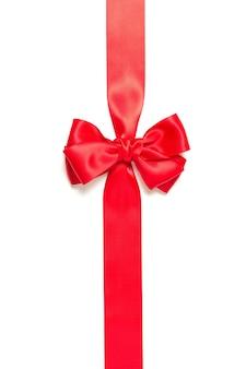 Fiocco regalo rosso e nastro rosso incrociato verticalmente isolato su sfondo bianco.