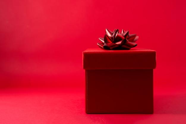 Confezione regalo rossa su sfondo rosso con spazio di copia