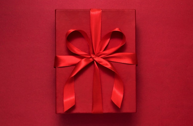 Confezione regalo rossa su sfondo rosso con nastro rosso - concetto di saluto