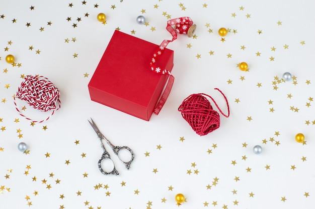 Scatola regalo rossa, nastri, confetti a stelle dorate, forbici