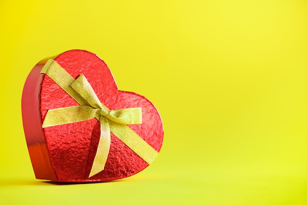 Contenitore di regalo rosso a forma di cuore su sfondo giallo. san valentino. concetto di amore romantico.