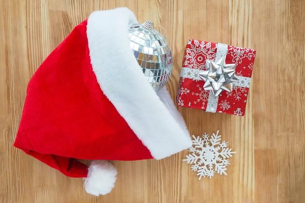Confezione regalo rossa, fiocco di neve e palla da discoteca cadono dal cappello rosso della santa su legno