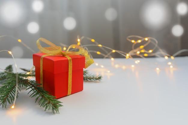 Confezione regalo rossa legata con nastro d'oro su un tavolo luminoso con luci bokeh e sfondo sfocato.