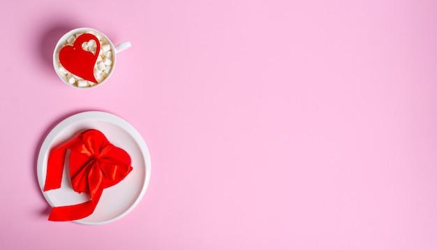 Contenitore di regalo rosso sul piatto bianco e una tazza bianca con marshmallow e un cuore di legno sul rosa