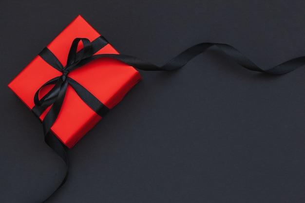 Confezione regalo rossa con nastro nero su sfondo nero