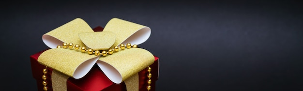 Confezione regalo rossa con fiocco oro e perline su uno spazio nero