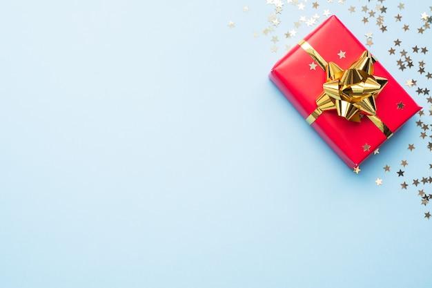 Confezione regalo rossa con coriandoli oro su sfondo blu. lay piatto.