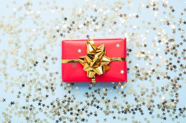 Confezione regalo rossa con coriandoli oro, vista dall'alto