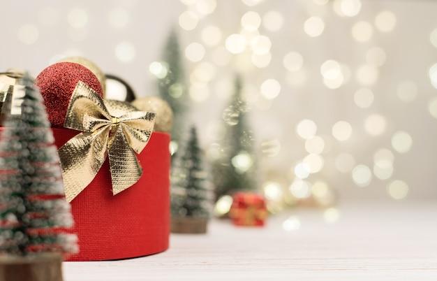 Confezione regalo rossa con un fiocco dorato con alberi di natale
