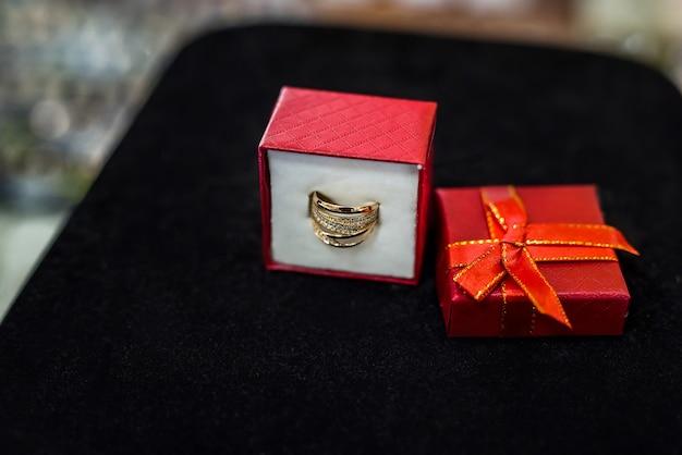 Confezione regalo rossa con anello dorato su sfondo nero