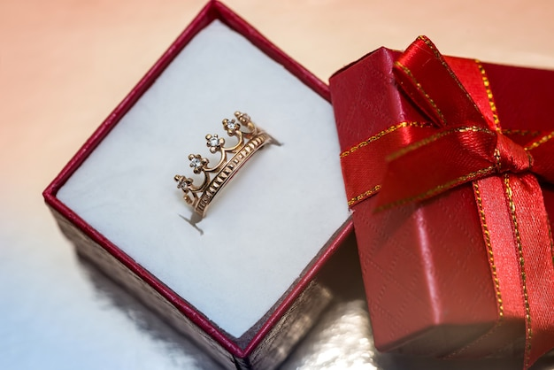 Confezione regalo rossa con anello dorato come corona