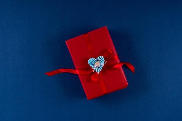 Confezione regalo rossa con cuore e fiocco su sfondo di colore blu classico 2020. concetto di imballaggio di san valentino 14 febbraio. disposizione piatta, copia spazio, vista dall'alto.