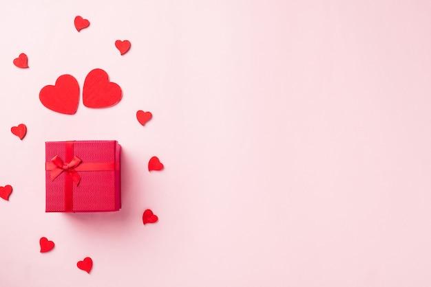 Confezione regalo rossa con fiocco in nastro e biglietto di auguri composizione a forma di cuori rossi in legno per amore