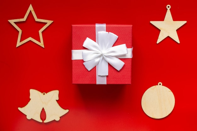 Confezione regalo rossa con fiocco bianco e decorazioni natalizie in legno vuote a forma di stelle, campane e palla, su fondo rosso. vista dall'alto.