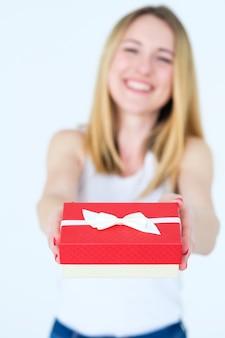 Confezione regalo rossa nelle mani della donna. regalo di festa o ricompensa di felice anniversario per una persona cara