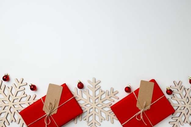 Contenitori di regalo rossi e bagattelle di natale sulla vista superiore del fondo bianco