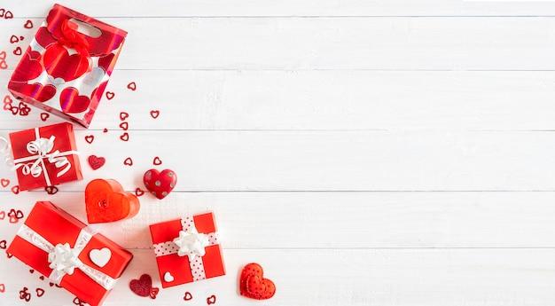 Contenitori di regalo rossi e piccole decorazioni del cuore su fondo di legno bianco