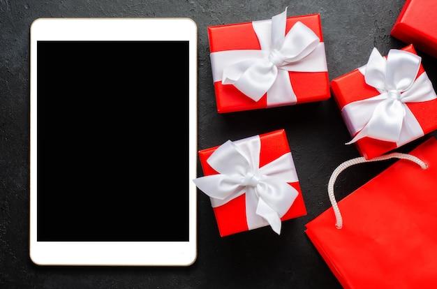 Contenitori di regalo rossi e un tablet con uno schermo vuoto per il testo. copia spazio.
