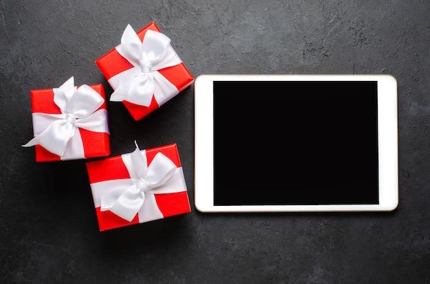 Contenitori di regalo rossi e un tablet con uno schermo vuoto