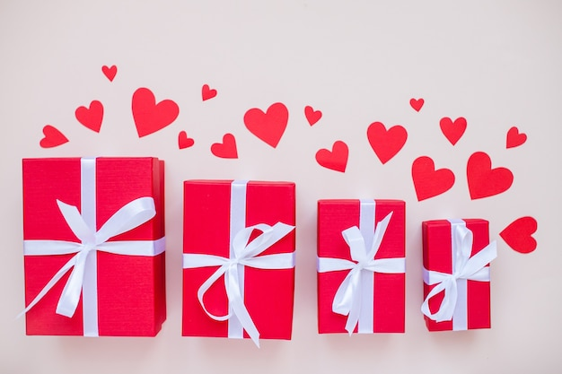 Scatole regalo rosse di varie dimensioni legate con un nastro di raso bianco e cuori rossi