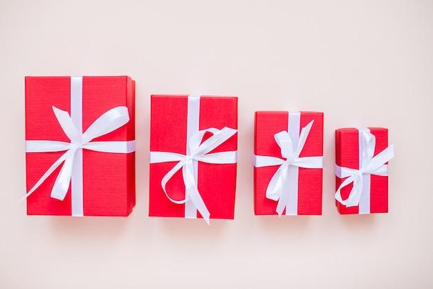 Scatole regalo rosse di varie dimensioni legate con un nastro di raso bianco