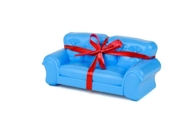 Nastro regalo rosso sul divano blu isolato su bianco. un campione di bellissimi mobili per la casa. minimalista.