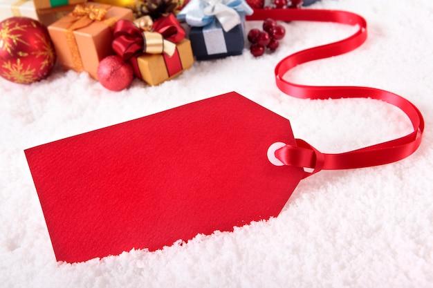 Etichetta rossa del regalo che mette su una neve con i vari regali e decorazioni di natale, spazio della copia