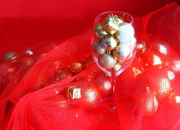Sfondo di natale rosso e oro con decorazioni natalizie in vetro di vite e oro al suo interno. bicchiere di vino con decorazioni natalizie