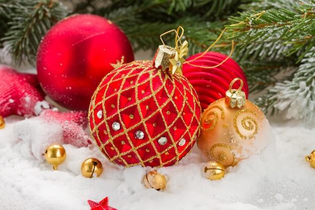 Palla di natale rossa e oro nella neve sotto l'albero di abete