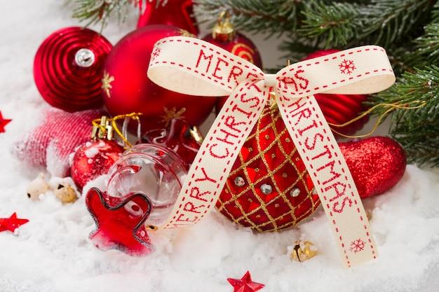 Palla di natale rossa e oro con nastro di buon natale in nevicata sotto l'abete