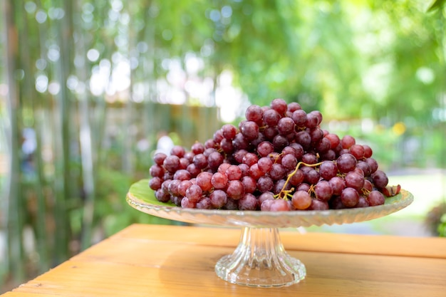 L'uva rossa sulla lastra di vetro del gradino sta da sola sulla tavola di legno nel bokeh della sfuocatura del campo del giardino all'aperto.