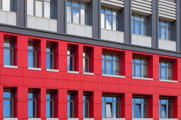 Facciata ventilata moderna rosso-grigia con finestre.