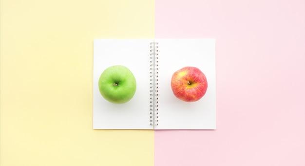Il piatto rosso e verde della mela giaceva sulla scrivania color pastello