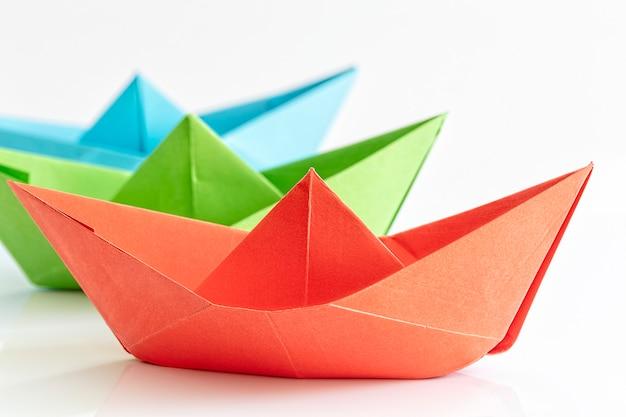 Barca di carta rossa, verde, blu isolata su priorità bassa bianca
