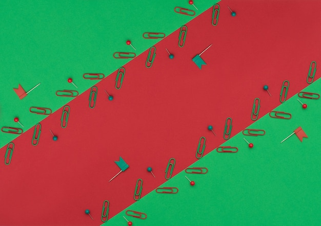 Clip e perni rossi e verdi su doppio sfondo verde e rosso. forniture scolastiche e per ufficio