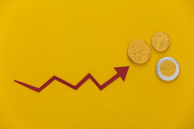 Freccia e monete rosse di crescita su giallo. grafico a freccia che sale. la crescita economica