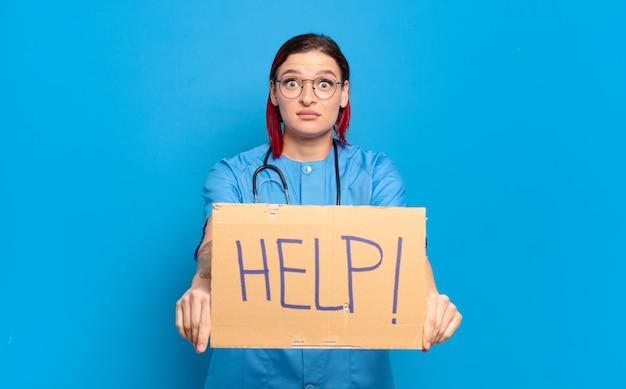 Donna fresca dell'infermiera dei capelli rossi. concetto di crisi medica