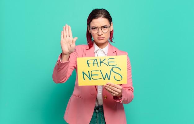 Concetto di notizie false della donna fredda dei capelli rossi