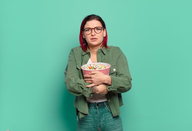 Donna fredda capelli rossi con popcorn e un telecomando della tv