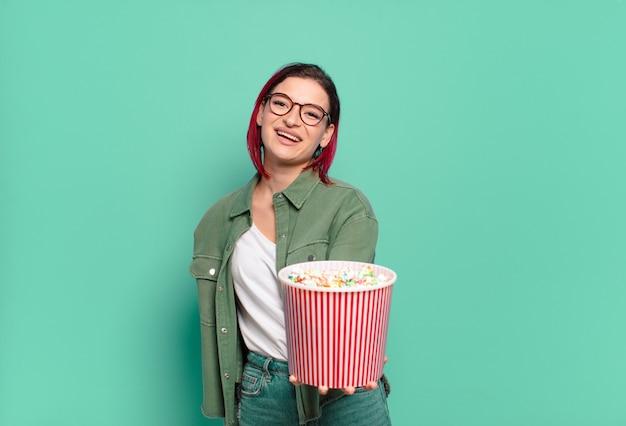 Donna fredda dei capelli rossi con popcorn e telecomando della tv
